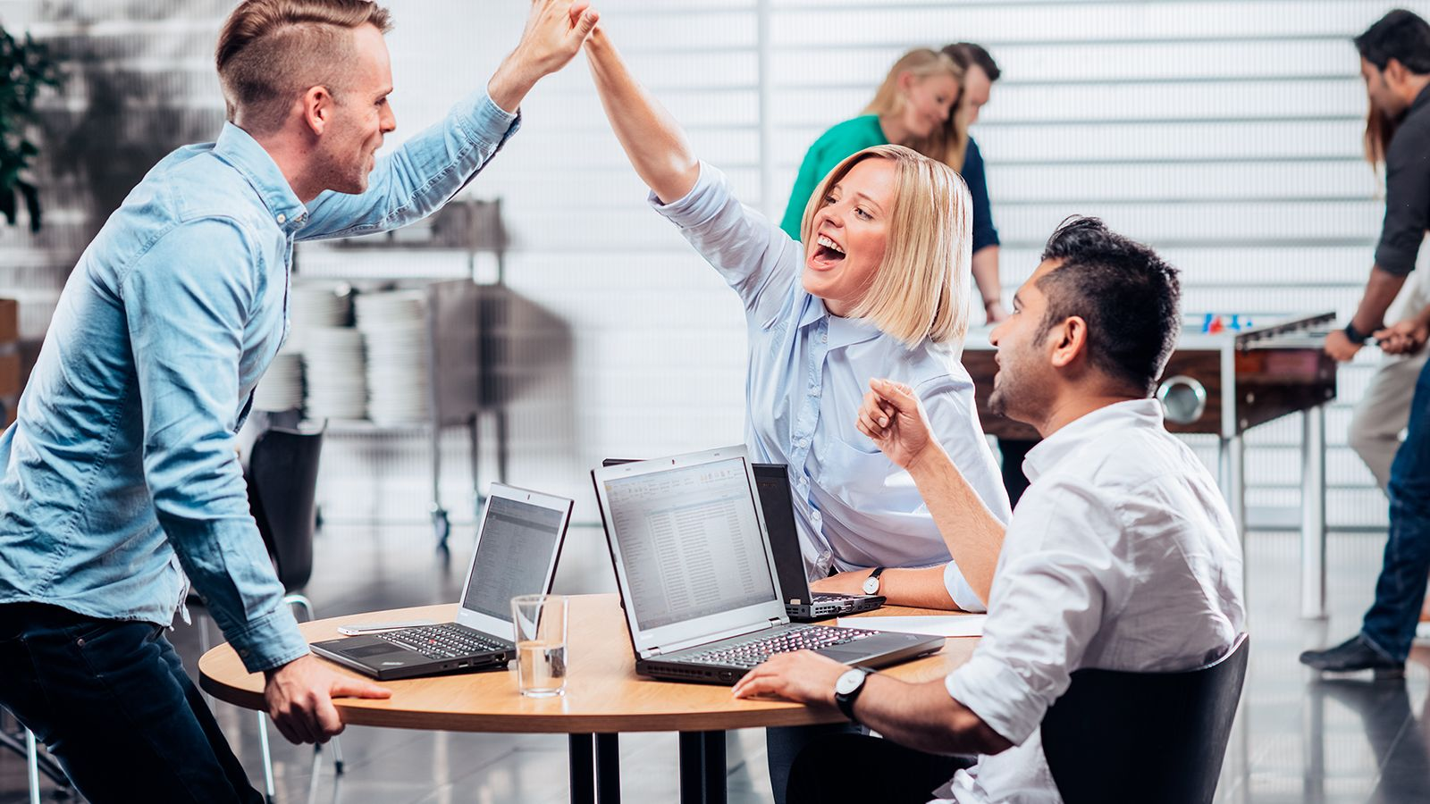 Happy coworkers in office giving high five